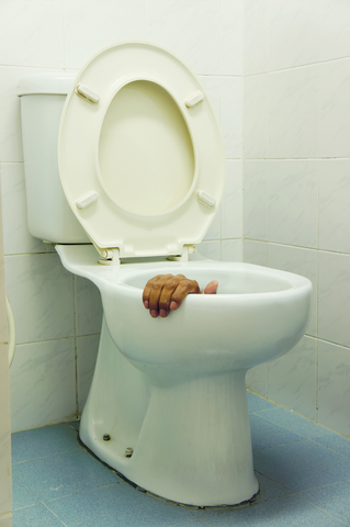 Man's hand in white toilet